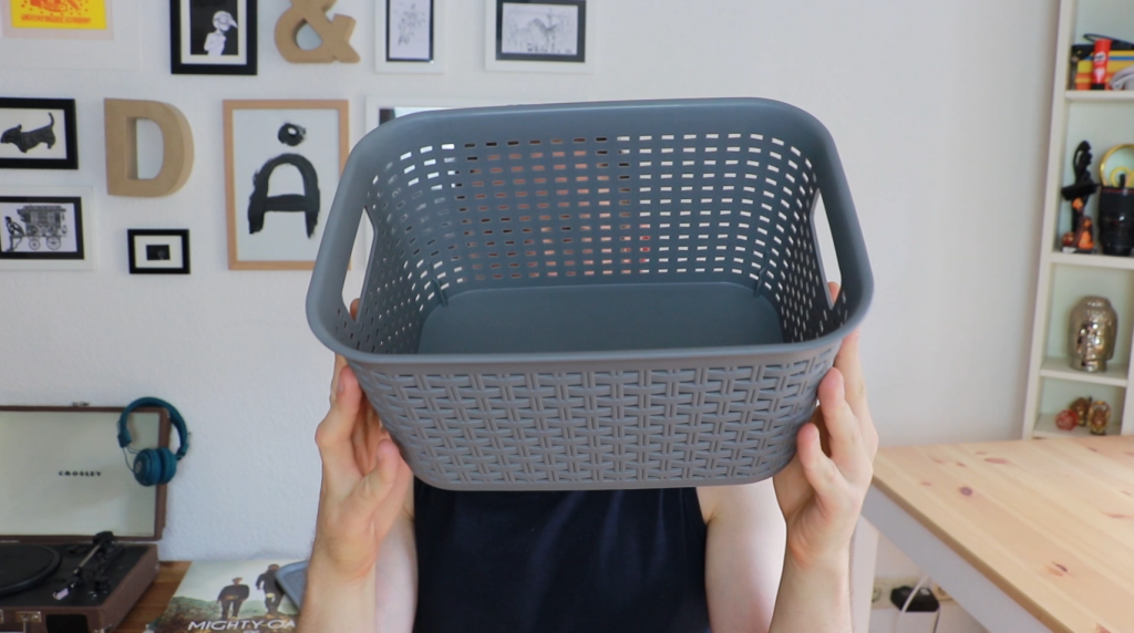 A grey basket to be used to hide cables in home office