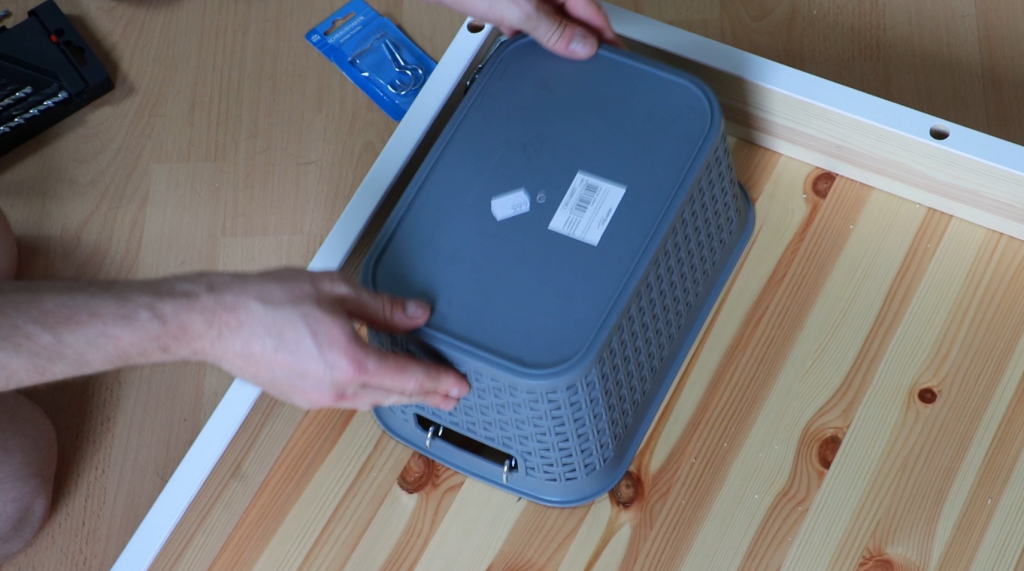Attaching a basket to the hooks in the desk top