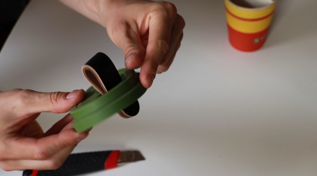 Attaching black leather handle to a coffee cup lid