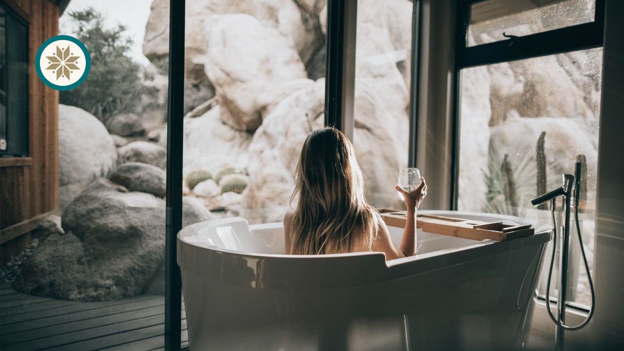 A woman is having a drink in the bathtub